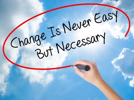 Woman Hand Writing Change Is Never Easy But Necessary with black marker on visual screen. Isolated on Sunny Sky. Business concept. Stock Photo