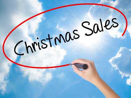 Woman Hand Writing Christmas Sales with black marker on visual screen. Isolated on Sunny Sky. Business,  internet concept. Stock Photo