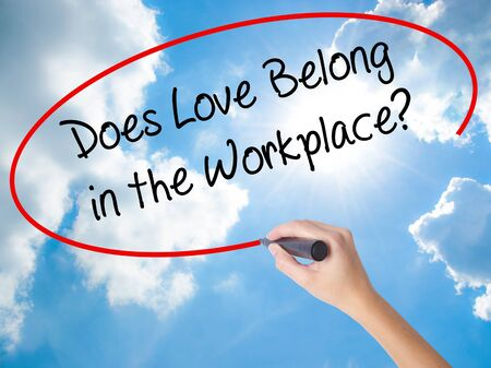 Woman Hand Writing Does Love Belong in the Workplace? with black marker on visual screen. Isolated on Sunny Sky. Business concept. Stock Photo