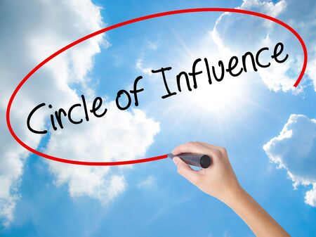 Woman Hand Writing Circle of Influence with black marker on visual screen. Isolated on Sunny Sky. Business concept. Stock Photo