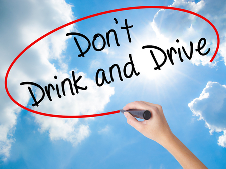 Woman Hand Writing Dont Drink and Drive with black marker on visual screen. Isolated on Sunny Sky. Life, technology, internet concept. Stock Image