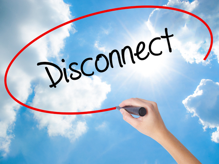 Woman Hand Writing Disconnect with black marker on visual screen. Isolated on Sunny Sky. Business concept. Stock Photo
