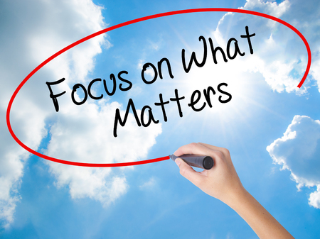 objectivism: Woman Hand Writing Focus on What Matters with black marker on visual screen. Isolated on Sunny Sky. Business concept. Stock Photo