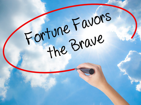 Woman Hand Writing Fortune Favors the Brave with black marker on visual screen. Isolated on Sunny Sky. Business concept. Stock Photo