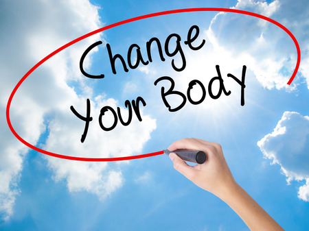 muscle gain: Woman Hand Writing Change Your Body with black marker on visual screen. Isolated on Sunny Sky. Business concept. Stock Photo