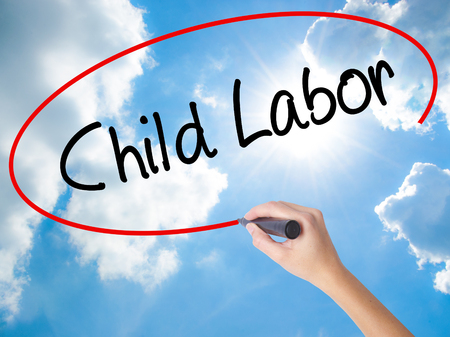 Woman Hand Writing Child Labor with black marker on visual screen. Isolated on Sunny Sky. Business concept. Stock Photo