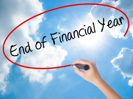 Woman Hand Writing End of Financial Year with black marker on visual screen. Isolated on Sunny Sky. Business concept. Stock Photo