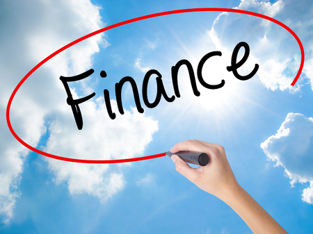 Woman Hand Writing Finance with black marker on visual screen. Isolated on Sunny Sky. Business concept. Stock Photo Stock Photo