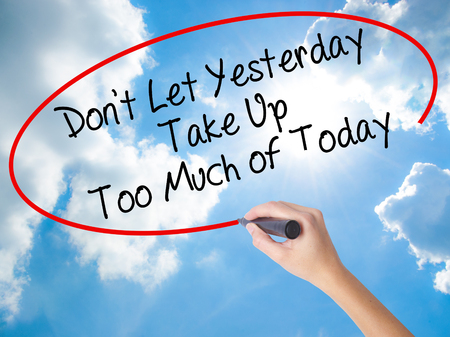 personal perspective: Woman Hand Writing Dont Let Yesterday Take Up Too Much of Today with black marker on visual screen. Isolated on Sunny Sky. Business concept. Stock Photo Stock Photo