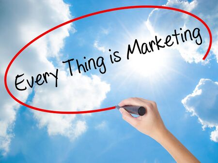 Woman Hand Writing  Every Thing is Marketing with black marker on visual screen. Isolated on Sunny Sky. Business concept. Stock Photo