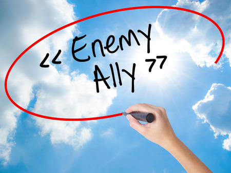 Woman Hand Writing Enemy - Ally with black marker on visual screen. Isolated on Sunny Sky. Business concept. Stock Photo