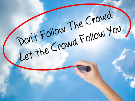 Woman Hand Writing Dont Follow The Crowd Let the Crowd Follow You with black marker on visual screen. Isolated on Sunny Sky. Business concept. Stock Photo