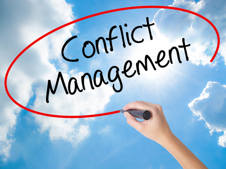 Woman Hand Writing Conflict Management with black marker on visual screen. Isolated on Sunny Sky. Business concept. Stock Photo Stock Photo