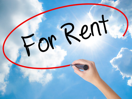 Woman Hand Writing For Rent with black marker on visual screen. Isolated on Sunny Sky. Business concept. Stock Photo
