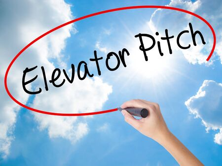 business pitch: Woman Hand Writing Elevator Pitch with black marker on visual screen. Isolated on Sunny Sky. Business concept. Stock Photo