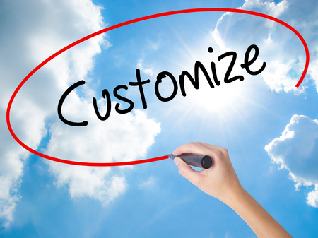 Woman Hand Writing  Customize with black marker on visual screen. Isolated on Sunny Sky. Business concept. Stock Photo