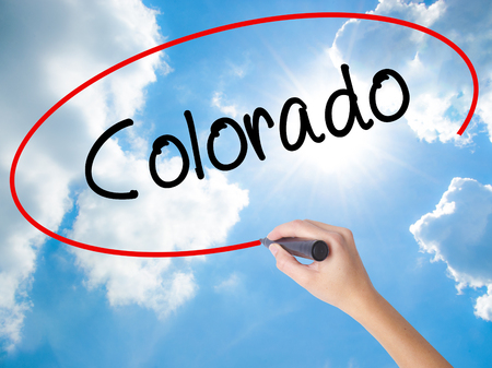 Woman Hand Writing Colorado  with black marker on visual screen. Isolated on Sunny Sky. Business, technology, internet concept.