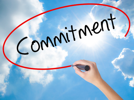 Woman Hand Writing Commitment with black marker on visual screen. Isolated on Sunny Sky. Business concept. Stock Photo