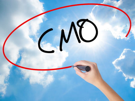 chief executive officer: Woman Hand Writing CMO (Chief Marketing Officer)   with black marker on visual screen. Isolated on Sunny Sky. Business concept. Stock Photo