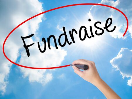 Woman Hand Writing Fundraise with black marker on visual screen. Isolated on Sunny Sky. Business,  technology, internet concept. Stock Photo