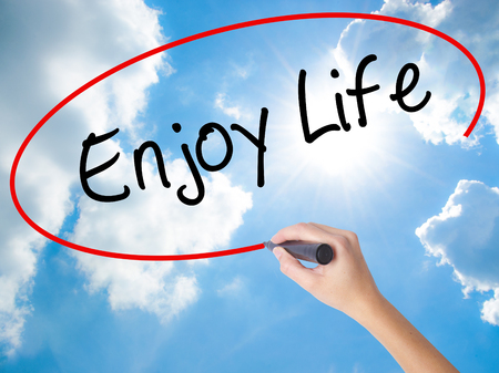 Woman Hand Writing Enjoy Life with black marker on visual screen. Isolated on Sunny Sky. Business concept. Stock Photo