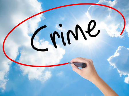 Woman Hand Writing Crime with black marker on visual screen. Isolated on Sunny Sky. Business concept. Stock Photo
