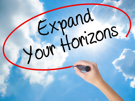 Woman Hand Writing  Expand Your Horizons  with black marker on visual screen. Isolated on Sunny Sky. Business concept. Stock Photo