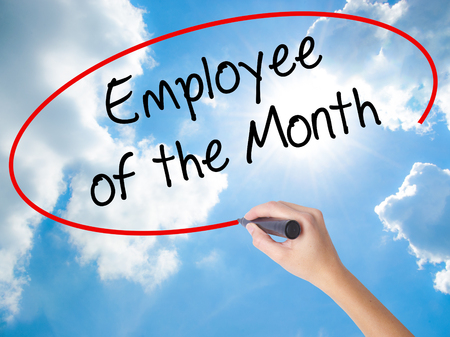 Woman Hand Writing Employee of the Month  with black marker on visual screen. Isolated on Sunny Sky. Business concept. Stock Photo