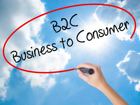 Woman Hand Writing B2C Business to Consumer with black marker on visual screen. Isolated on Sunny Sky. Business concept. Stock Photo