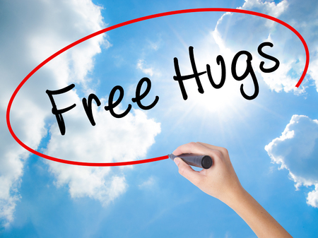 Woman Hand Writing Free Hugs with black marker on visual screen. Isolated on Sunny Sky. Business concept. Stock Photo Stock Photo