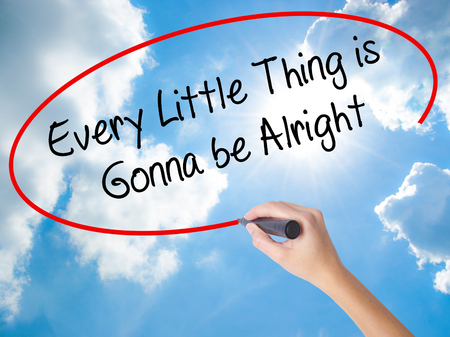 alright: Woman Hand Writing Every Little Thing is Gonna be Alright with black marker on visual screen. Isolated on Sunny Sky. Business, technology, internet concept.