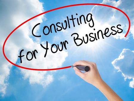 Vrouw Hand schrijven Consulting voor uw bedrijf met zwarte marker op visuele scherm. Geïsoleerd op zonnige hemel. Bedrijfsconcept. Stock foto