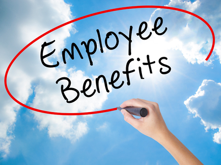 Woman Hand Writing Employee Benefits with black marker on visual screen. Isolated on Sunny Sky. Business concept. Stock Photo