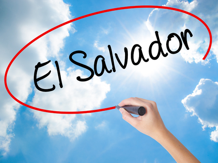 Woman Hand Writing El Salvador with black marker on visual screen. Isolated on Sunny Sky. Business concept. Stock Photo