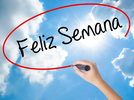 Woman Hand Writing Feliz Semana  (Happy Week in SpanishPortuguese) with black marker on visual screen. Isolated on Sunny Sky. Business concept. Stock Photo Stock Photo