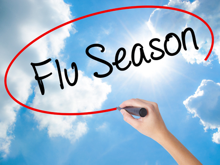 Woman Hand Writing  Flu Season with black marker on visual screen. Isolated on Sunny Sky. Business concept. Stock Photo Stock Photo