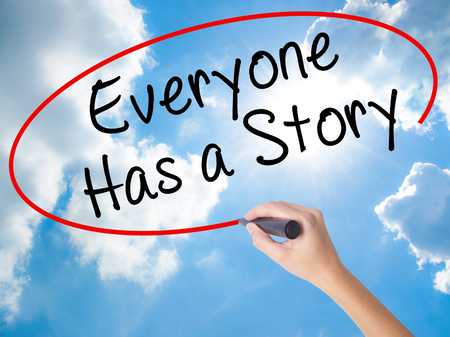 Woman Hand Writing Everyone Has a Story with black marker on visual screen. Isolated on Sunny Sky. Business concept. Stock Photo