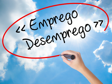 Woman Hand Writing Emprego Desemprego (Employment - Unemployment in Portuguese)  with black marker on visual screen. Isolated on Sunny Sky. Business concept. Stock Photo Stock Photo