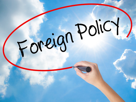Woman Hand Writing Foreign Policy with black marker on visual screen. Isolated on Sunny Sky. Business concept. Stock Photo