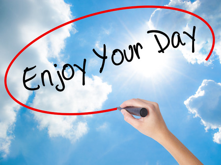 Woman Hand Writing Enjoy Your Day with black marker on visual screen. Isolated on Sunny Sky. Business concept. Stock Photo