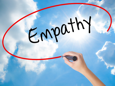 pity: Woman Hand Writing Empathy with black marker on visual screen. Isolated on Sunny Sky. Business concept. Stock Photo