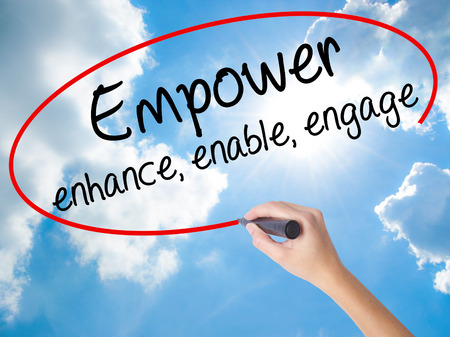 decisionmaking: Woman Hand Writing Empower enhance, enable, engage with black marker on visual screen. Isolated on Sunny Sky. Business concept. Stock Photo