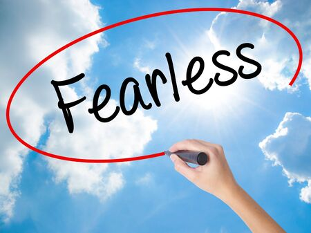unafraid: Woman Hand Writing Fearless  with black marker on visual screen. Isolated on Sunny Sky. Business concept. Stock Photo