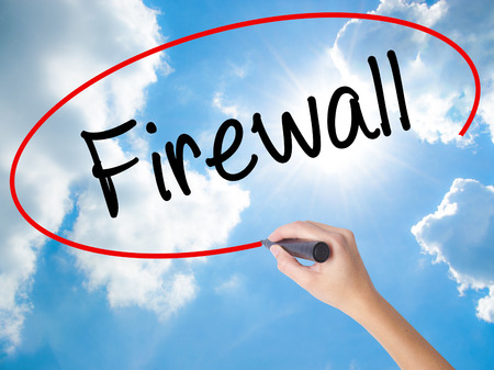 Woman Hand Writing Firewall  with black marker on visual screen. Isolated on Sunny Sky. Business concept. Stock Photo