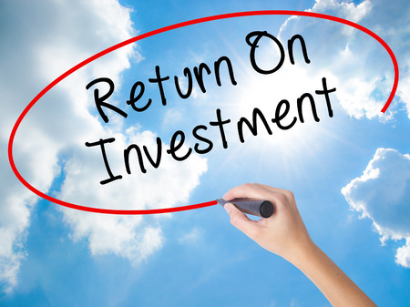 Woman Hand Writing Return On Investment  with black marker on visual screen. Isolated on Sunny Sky. Business concept. Stock Photo