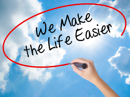 Woman Hand Writing We Make the Life Easier with black marker on visual screen. Isolated on Sunny Sky. Business concept. Stock Photo Stockfoto