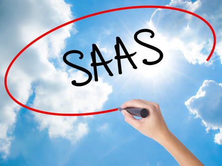 Woman Hand Writing SAAS with black marker on visual screen. Isolated on Sunny Sky. Business concept. Stock Photo