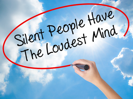 Woman Hand Writing Silent People Have The Loudest Mind with black marker on visual screen. Isolated on Sunny Sky. Business concept. Stock Photo