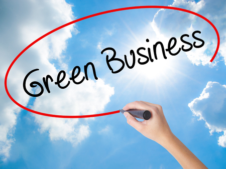 Woman Hand Writing Green Business with black marker on visual screen. Isolated on Sunny Sky. Business, technology, internet concept. Stock Photo
