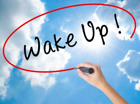 modify: Woman Hand Writing Wake Up with black marker on visual screen. Isolated on Sunny Sky. Business concept. Stock Photo